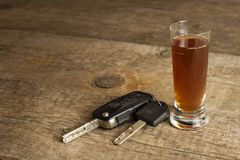 Alcohol and driving. Danger on the roads. Alcoholic behind the wheel. Car keys on the bar. Royalty Free Stock Image