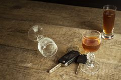 Alcohol and driving. Danger on the roads. Alcoholic behind the wheel. Car keys on the bar. Royalty Free Stock Photo