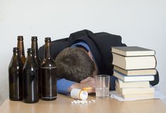 Alcohol, drugs, and work. Businessman sleeping at his desk, surrounded by books, drugs and alcohol Royalty Free Stock Image
