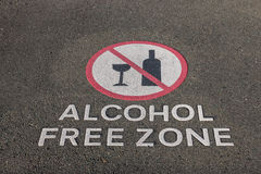 Alcohol free zone sign on pavement. Closeup of alcohol free zone sign on pavement stock photo