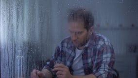 Alcohol gewijde mens het drinken wodka in eenzaamheid achter regenachtig venster, problemen stock videobeelden