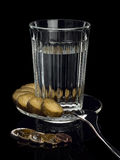 Alcohol in a glass with snack and EURO coins. Royalty Free Stock Photography