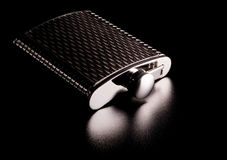 Alcohol grooved flask isolated on black Stock Photo