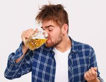 Alcohol. Guy in blue shirt with beer Royalty Free Stock Images