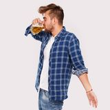 Alcohol. Guy in blue shirt with beer Stock Images