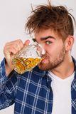Alcohol. Guy in blue shirt with beer Stock Photography