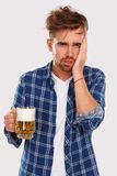 Alcohol. Guy in blue shirt with beer Royalty Free Stock Photos