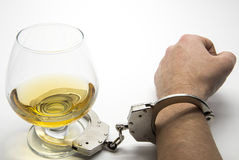 Alcohol and handcuffs. Alcohol addiction concept Stock Images