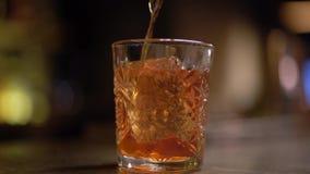 Alcohol met één stuk van ijs bij lijst die dichte omhooggaand wordt geschoten Het oranje vloeibare gieten in het glas langzaam stock videobeelden