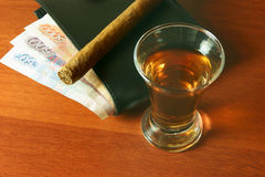 Alcohol, money and a cigar Royalty Free Stock Image