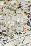 Alcohol and money. Two glasses filled with vodka are on dollar bills Stock Photos
