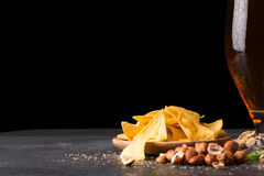 Alcohol and nutritious food on a black background. Classic nachos and roasted nuts. Pub concept. Copy space. Stock Photography