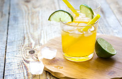 Alcohol orange cocktails with lime and ice on wooden background Stock Photo