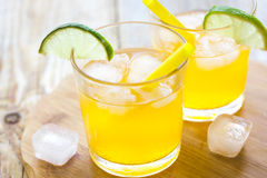 Alcohol orange cocktails with lime and ice on wooden background Royalty Free Stock Image
