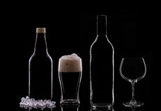 Alcohol. A Pint of Dark Beer, a Beer Bottle, a Wine Bottle and a Wine Glass on Black Background royalty free stock photography