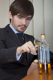 Alcohol problem. Man in business suit drinking by the work Royalty Free Stock Photos