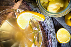 Alcohol quince liqueur sliced fruit jar wooden cups Royalty Free Stock Photos