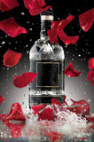 An alcohol romance. A photo of luxury alcohol bottle with falling rose leaves Royalty Free Stock Photography