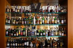 Well stocked bar with various alcoholic bottles and glasses royalty free stock photo