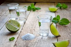 Alcohol Shot Drink. Silver Tequila with Lime, Salt and Green on the Wooden Table Royalty Free Stock Photos