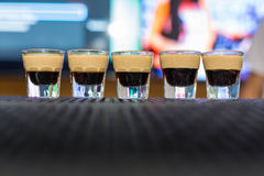 Alcohol shots on ther bar with B52 inside. Five Alcohol shots on ther bar with B52 inside royalty free stock images