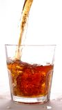Alcohol splash. Alcohol flow into the glass with splash Royalty Free Stock Photography
