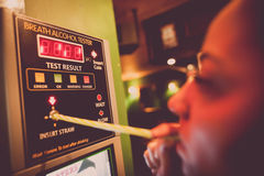 Alcohol tester on a wall. Close up shot of an alcohol tester on a wall, and a person blowing through a straw royalty free stock images