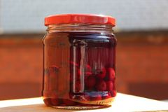 Alcohol. Tincture of cherries in the moonshine. The tincture of cherries in the moonshine. Alcohol drink. Red colours stock photos
