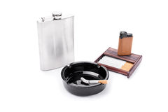 Alcohol and tobacco. Flask, ashtray, some cigarettes and lighter on a cigarette case isolated on white background royalty free stock photos