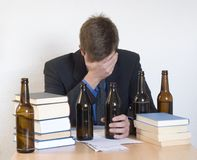Alcohol and Work. Businessman sitting in his office with papers, books and beer bottles Royalty Free Stock Photos