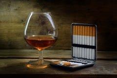 Alcohol y tabaco, vidrio con el coñac o brandy y un caso con imagen de archivo