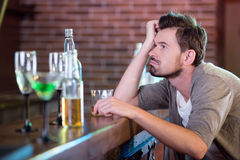 Alcohol. Young drunk man drinking alcohol in the bar Stock Image