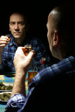 Alcoholic. Lonely drinking  man with reflection in mirror Royalty Free Stock Photography