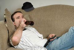 Alcoholic. A young alcoholic lying on the couch drinking from a bottle of beer while watching tv Stock Photo
