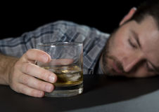 Alcoholic addict man drunk sleeping holding whiskey glass in alcoholism concept. Alcoholic wasted man sleeping lying head on table and being drunk holding Stock Image
