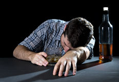 Alcoholic addict man drunk sleeping holding whiskey glass in alcoholism concept. Alcoholic wasted man sleeping lying head on table and being drunk holding royalty free stock photography