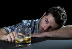 Alcoholic addict man drunk with whiskey glass in alcoholism concept. Grunge messy alcoholic man drunk at the table in a bar with whiskey glass in alcohol royalty free stock image