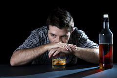 Alcoholic addict man drunk with whiskey glass in alcoholism concept. Grunge messy alcoholic man drunk at the table in a bar with whiskey glass in alcohol Stock Photos