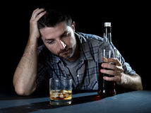 Alcoholic addict man drunk with whiskey glass in alcoholism concept. Grunge messy alcoholic man drunk at the table in a bar with whiskey bottle looking at glass stock photography