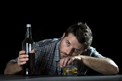 Alcoholic addict man drunk with whiskey glass in alcoholism concept. Grunge messy alcoholic man drunk at the table in a bar holding whiskey glass and bottle in stock images