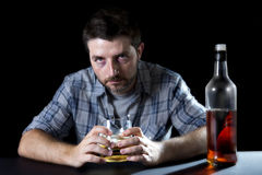 Alcoholic addict man drunk with whiskey glass in alcoholism concept. Grunge alcoholic man drunk and wasted  at the table with whiskey glass in his hands and Royalty Free Stock Images