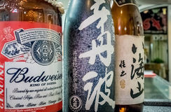 Alcoholic beverages. Bottles of American beer and Japanese wine displayed side by side in the Gyoza no Osho restaurant, Waikiki, Honolulu, Hawaii, USA Stock Image