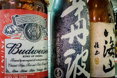 Alcoholic beverages. Bottles of American beer and Japanese wine displayed side by side in a restaurant, Waikiki, Honolulu, Hawaii, USA Stock Photos