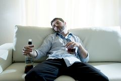 Alcoholic Business man wearing blue loose tie drunk with whiskey bottle on couch Stock Photography