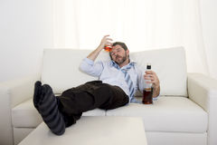 Alcoholic Business man wearing blue loose tie drunk with whiskey bottle on couch Royalty Free Stock Photos