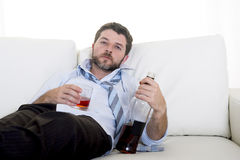 Alcoholic Business man wearing blue loose tie drunk with whiskey bottle on couch Stock Images