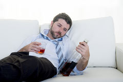 Alcoholic Business man wearing blue loose tie drunk with whiskey bottle on couch Royalty Free Stock Image
