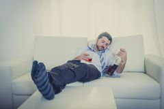 Alcoholic Businessman in loose tie drunk wasted on couch at home Stock Image