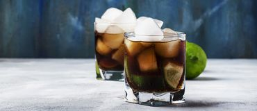 Alcoholic cocktail cuba libre with ice, lime, juice, cola and golden rum, gray bar counter background, selective focus royalty free stock image