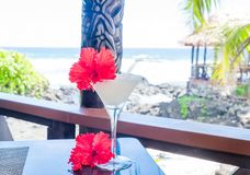 Alcoholic cocktail drink with red hibiscus flower garnish with w. Ooden carving in background at beach bar on Upolu Island, Western Samoa, South Pacific royalty free stock photography